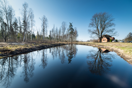 reflections of country house in the pond with trees and blue sky