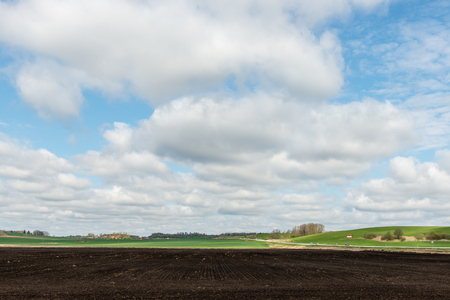stock vista: countryside fields in early spring with clouds and farmland