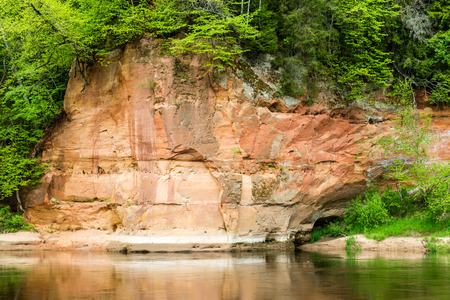 cavern: sandstone cliffs by the river in Gauja national park in latvia Stock Photo