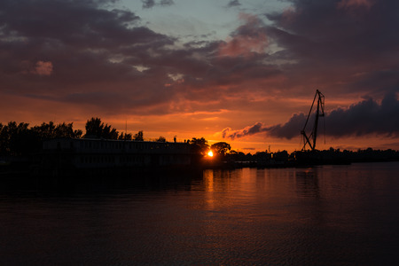 reddish sunset over sea port with cranes in background