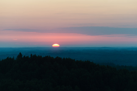 Dramatic sunrise over dark forest with red clouds