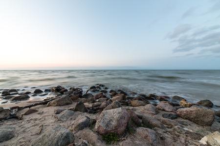 Rotsachtig strand met wolken en water Stockfoto
