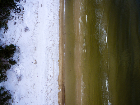 cleared: aerial view of frozen beach in winter. drone photography. sea with waves. Stock Photo