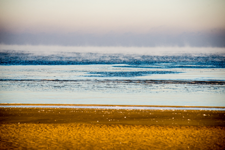 frozen beach view by the baltic sea with sand and ice in water Stock Photo