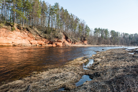 frozen river in winter with sandstone cliffs and ice blocks. Gauja National Park. Latvia.