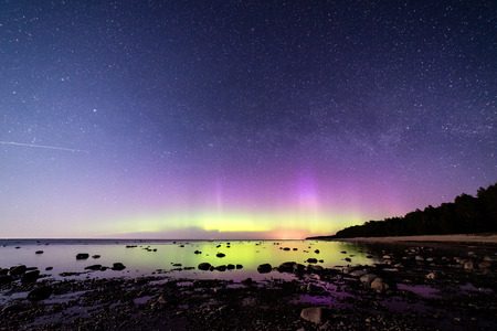 ionosphere: Intense northern lights (Aurora borealis) over Baltic sea. rocky beach Stock Photo