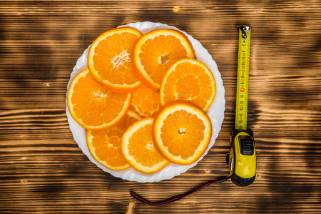 dish of sliced oranges on burnt wooden desk with measurement tape. food pattern Stock Photo