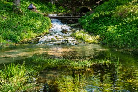 beautiful river in forest with reflections and trees on both sides of the stream Stock Photo