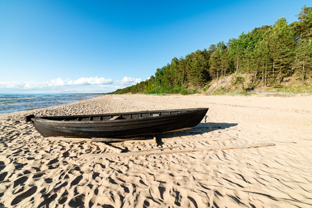 comfortable beach of the baltic sea with rocks and green vegetation and old boat in summer Stok Fotoğraf