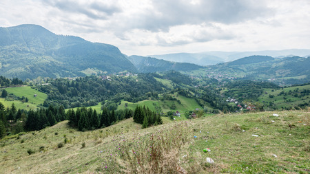 View to the carpathian mountains and romanian village from the top with lonely trees and clouds above Stock Photo