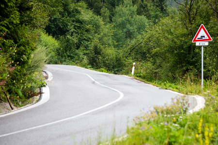 the arable land: mountain country road in summer at countryside with trees around