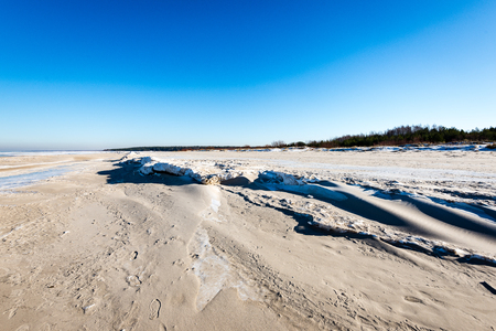 frozen beach in cold winters day with colorful sky and ice Stock Photo