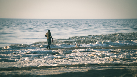 people enjoying frozen beach in winters cold. walking and relaxing