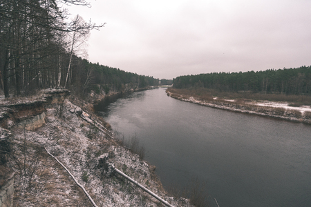 frozen countryside scene in winter with snow. calm river with bridge
