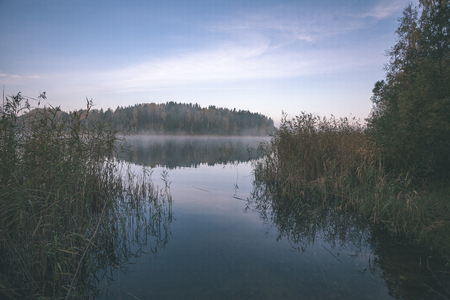 misty countryside landscape with lake in latvia in autumn. cold morning - vintage look