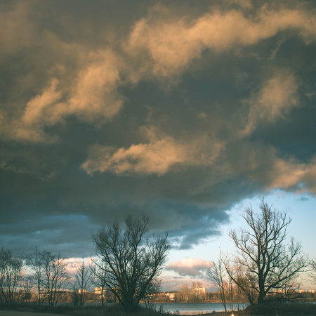 Dark storm clouds over meadow with green grass and mountains in background - instant vintage square photo Stock Photo
