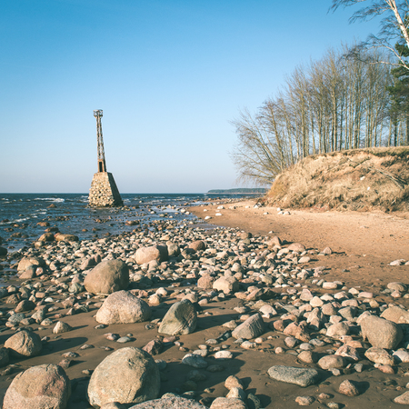 old ruins of lighthouse on the shore of Baltic beach - instant vintage square photo