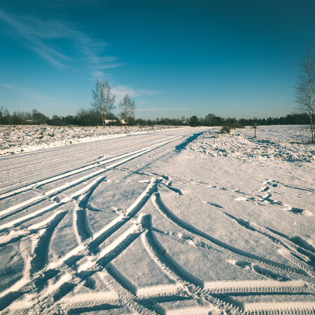 covered fields: snowy winter road with tire markings and blue sky - instant vintage square photo Stock Photo