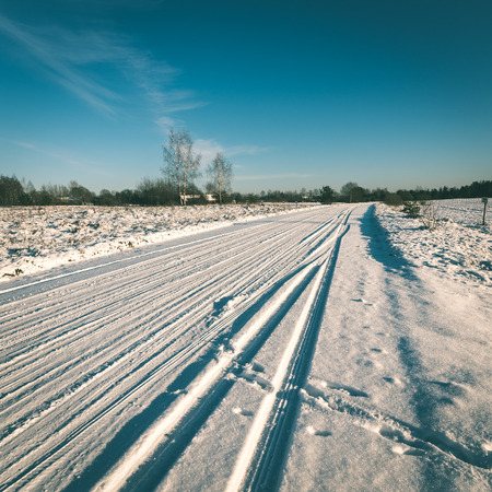 snowy winter road with tire markings and blue sky - instant vintage square photo Stock Photo