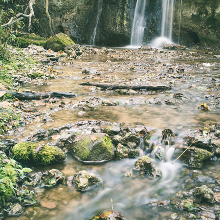 waterfall in the forest in late autumn - instant vintage square photo Stock Photo