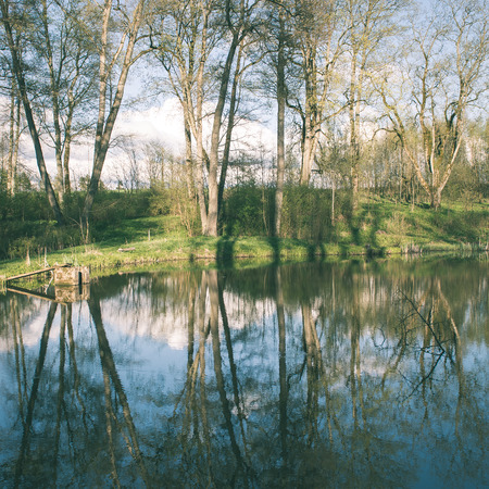 flood area: scenic and beautiful reflections of trees and clouds in water of the river - instant vintage square photo Stock Photo