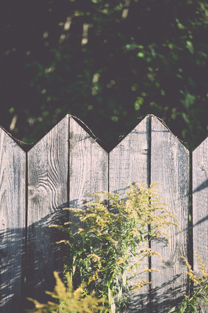 rusty nail: old wooden fence with barbed wire on top - retro, vintage style look