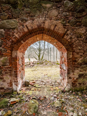 ruins of old abandoned church with red bricks and stone in early spring in Latvia