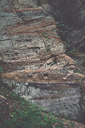 teutonic: sandstone cliffs with inscriptions near tourist trails - retro, vintage style look Stock Photo