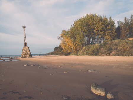 sunspot: Shoreline of Baltic sea beach with rocks and sand dunes under clouds - retro, vintage style look