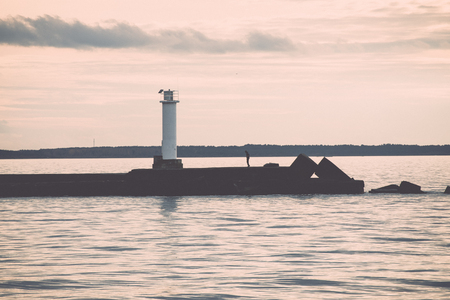 breakwater in the sea with lighthouse on it near Riga, latvia - retro, vintage style look Stock Photo