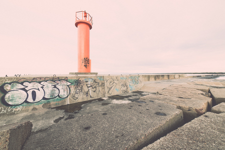 breakwater in the sea with lighthouse on it near Riga, latvia - retro, vintage style look Imagens