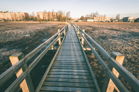 morass: wooden boardwalk with bird watch tower in early morning with colorful sunrise in Liepaja, Latvia - vintage green look