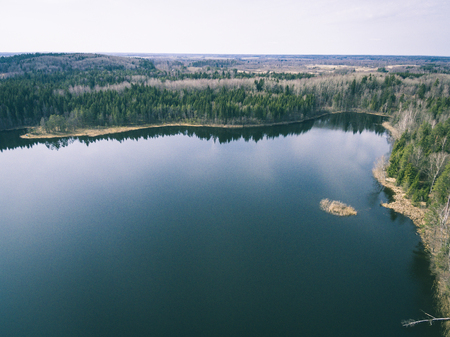cleared: drone image. aerial view of rural area with forest lake in bright sunlight - vintage look Stock Photo
