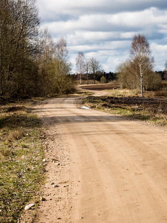 Winding country Road with clouds above and gravel surface surrounded by trees