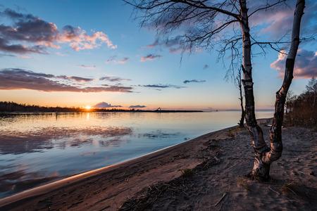 dramatic sunrise over the calm river in spring. sun showing through the trees. Daugava, Latvia