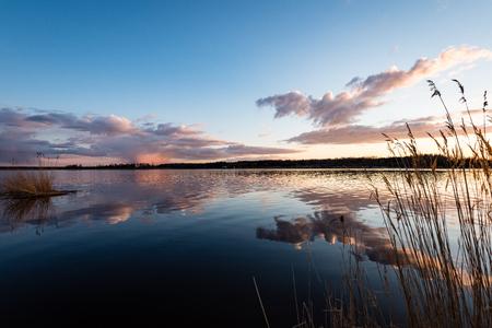 dramatic sunrise over the calm river in spring. Daugava, Latvia
