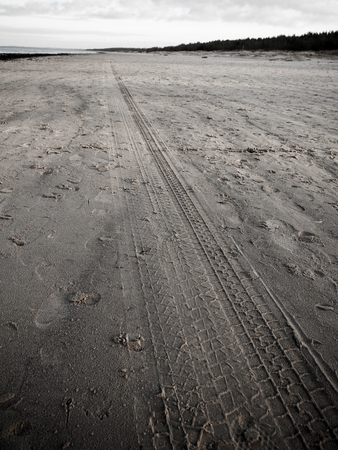 car tyre tracks on the beach sand in perspective - retro vintage 80s film look Stock Photo