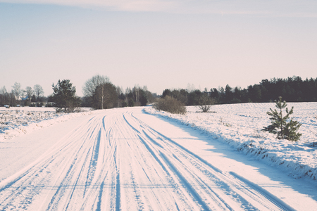 winter tires: snowy winter road with tire markings and blue sky - retro vintage effect