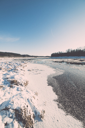 covered fields: beautiful snowy winter landscape with frozen river and blue sky - retro vintage effect