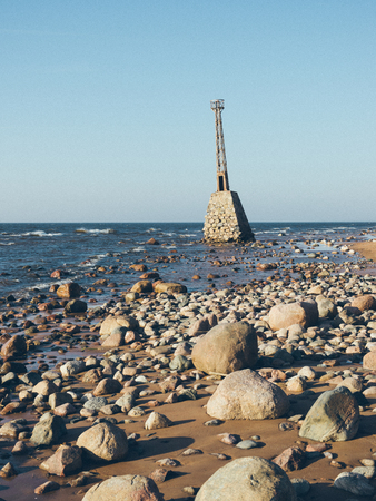 old ruins of lighthouse on the shore of Baltic beach - grainy retro vintage film effect