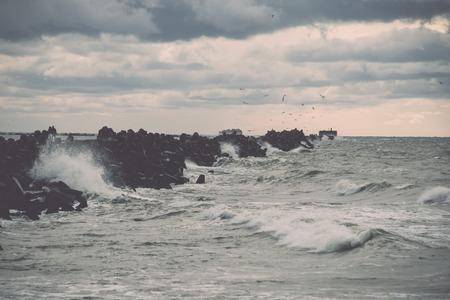 Les vagues écrasent les rochers et les ruines du vieux fort au coucher du soleil sur la plage - rétro effet film vintage Banque d'images - 77845920