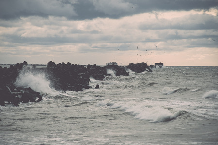 waves crushing over rocks and ruins of old fort at sunset on the beach - retro vintage film effect
