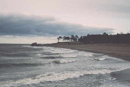 Les vagues écrasent les rochers et les ruines du vieux fort au coucher du soleil sur la plage - rétro effet film vintage Banque d'images - 77845923