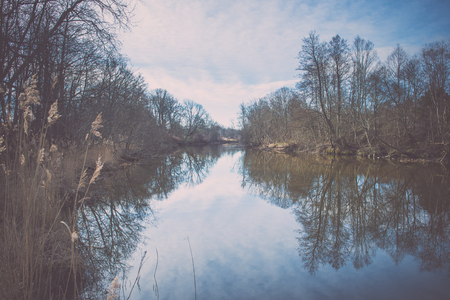 a situation alone: dramatic clouds over the river in misty morning in spring with reflections in water - retro vintage looking effect