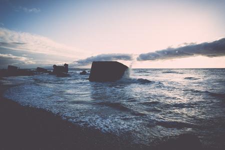 Les vagues écrasent les rochers et les ruines du vieux fort au coucher du soleil sur la plage - rétro effet film vintage Banque d'images - 77876897