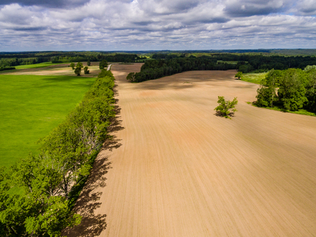 drone image. aerial view of rural area with freshly cultivated fields. green and brown. summer