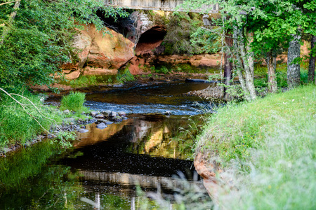 beautyful: beautyful morning light over forest river of Amata, Cesis, Latvia. sandstone cliffs and green vegetation around water in summer Stock Photo