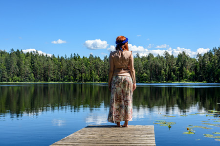 young woman enjoying nature on boardwalk in the lake with water lillies and cloud reflections Stock Photo