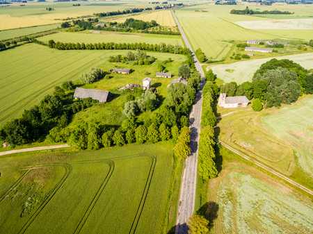 cleared: drone image. aerial view of rural area with green fields and forests in sunny summer day with countryside roads