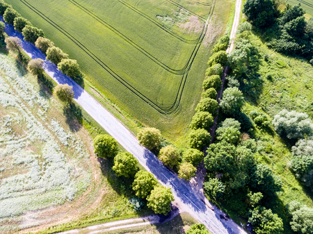 even: drone image. aerial view of rural area with green fields and forests in sunny summer day with countryside roads